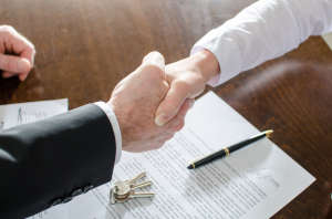 Two Hands Shaking Over Real Estate Contract